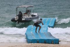 Men walking on the floating pier to the dinghy boat while it is windy and the waves stock images