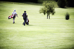 Men walking at golf course with bags. Two male golf player walking on fairway with their golf bags, plenty of copy-space Stock Image