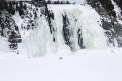 Men walking near frozen waterfall Royalty Free Stock Photos