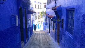 A men walking in street of the blue medina of town Chefchaouen in Morocco stock video