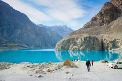 Men walking to ride a boat at the Attabad lake. stock image