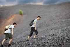 Men walks on stones slope Stock Photos