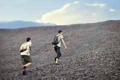 Men walks on stones slope Royalty Free Stock Images