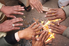 Men warm hands over the fire in India Stock Photos