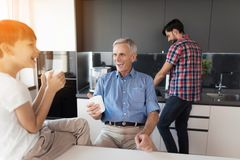 The old man and the boy laugh at something while the boy`s father washes the dishes behind them. The men washes the dishes, and behind him his elderly father and Royalty Free Stock Photography