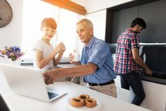 The old man is showing something to the boy on his gray laptop. Behind them, the man washes the dishes. A men washes the dishes while he is behind him, his stock image