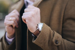 Men watches on hand in coat. Luxury expensive fashion watch wealthy man in brown coat Stock Photo