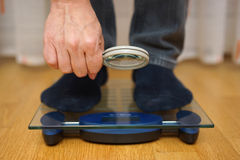 Men is watching his weight over the magnifying glass on scales Royalty Free Stock Image