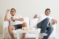Men watching live sport match on tv at home. Male friends watching a movie at home Royalty Free Stock Photo