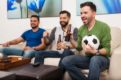 Men watching a soccer game on TV. Group of young men watching a soccer game at home and drinking some beer royalty free stock photography