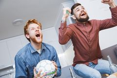 Men watching sport on tv together at home stand up cheering Stock Image