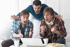 Men watching video on laptop. Handsome men watching video on laptop together Stock Photos