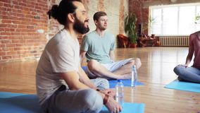 Men with water resting on yoga mats in gym stock footage