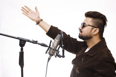Men Wearing brown coat and glasses singing into condenser microp Stock Photos