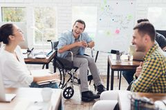 Office workers and man in a wheelchair discussing business moments in a modern office. Royalty Free Stock Photos