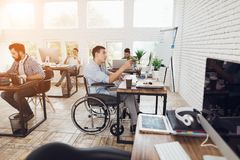 A man in a wheelchair is working in a bright office. A men in a wheelchair is working in a bright office. His colleagues are passionate about work. The men Stock Photography
