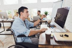 Disabled person in the wheelchair looks carefully at the computer. Stock Photos