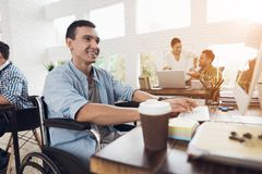 Disabled person in the wheelchair works in the office at the computer. Stock Photo