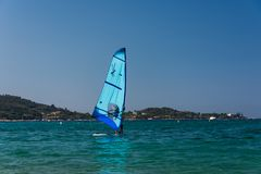The men is wind surfing on the Corsica blue sea. Blue wind surf in foreground, Corsica nature in background. royalty free stock photos