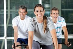 Men And Woman On Exercise Bikes Stock Photos