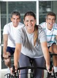 Men And Woman On Exercise Bikes Royalty Free Stock Photo