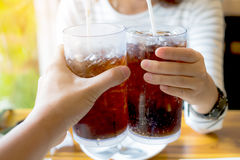 Men and Woman hand giving glass of cola. Glass of cola ,Soft drinks with ice, sweethart or buddy Royalty Free Stock Images