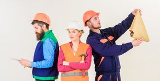 Men and woman in helmets carefree with hammer and project,