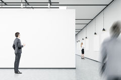 Men and a woman are looking at empty banners in an art gallery Royalty Free Stock Photos