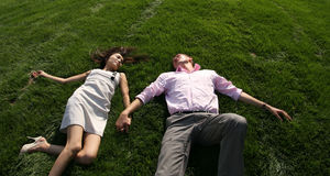 Men and woman lying on grass. To fall in love, men and woman lying on green grass Royalty Free Stock Photography