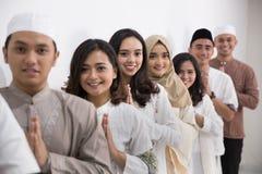 Men and woman muslim eid mubarak. Group of muslim asian men and women smiling and greeting. embracing each other during eid mubarak celebration Stock Image