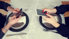 Men and woman playing with the phones. Men and woman playing with phones Royalty Free Stock Image
