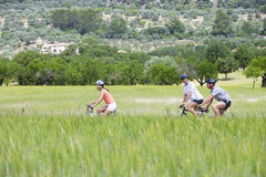 Men and woman riding bicycles through rural field Stock Photography