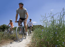 Men and woman riding bicycles on rural path Royalty Free Stock Images
