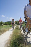 Men and woman riding bicycles on rural path stock photography