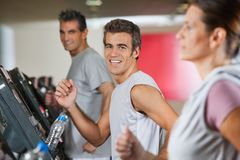 Men And Woman Running On Treadmill Stock Photography