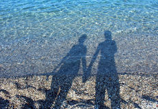 Men and woman shadows on water Royalty Free Stock Photography
