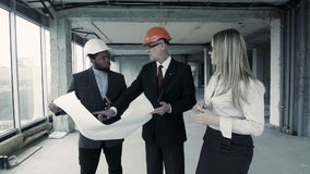 Men, woman in suit and helmet discuss blueprint, communicate with buyer. Chief engineer builder