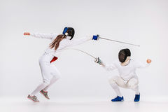The men and woman wearing fencing suit practicing with sword against gray Stock Photography
