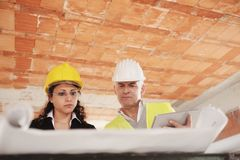 Female Architect and Foreman Meeting In Construction Site. Men and women working in construction site. Teamwork with foreman speaking with engineer and looking royalty free stock photography