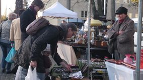 Men and women choose antiques at a flea market. Customers trade with sellers.