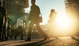 Business people walking on a busy street early in the morning. Men and women commuting to office early in the morning carrying office bags with sun flare in the Royalty Free Stock Photos