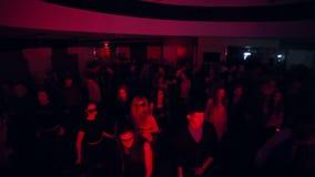 Men and women dance to sounds of music in night club. Jib shot