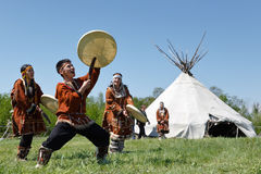 Men and women dancing with a tambourine on the grass on a background yaranga. Kamchatka, Russia Royalty Free Stock Image