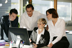 Men and women at desk with computer Stock Photography