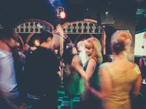 People dancing at a nightclub. Men and women dressed in vintage outfits dancing at a nightclub Stock Photo