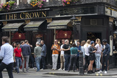 Men and women drink beer and smoke outside the Crown pub near Leicester square on a sunny day Stock Image
