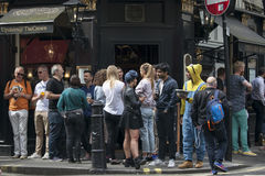 Men and women drink beer and smoke outside the Crown pub near Leicester square on a sunny day Stock Photos