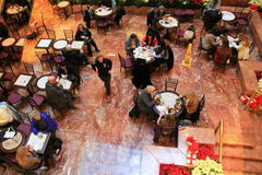 Men and women enjoying lunch in lobby restaurant of Trump Towers, NYC,2015 Stock Image