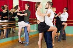Men and women enjoying of tango in class royalty free stock photography