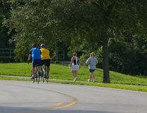 Men and Women Exercising In The Park. Different ways of exercising. Men on bicycles, women walking. Photographed at Walsingham Park in Largo Florida Stock Image